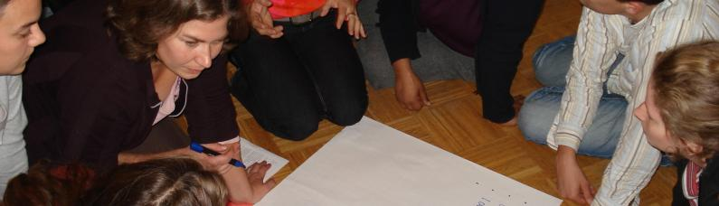 Some course participants work together to solve a creative task